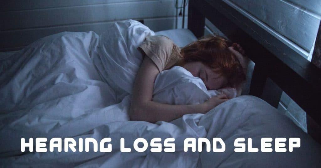 A woman sleeping in a dark room.